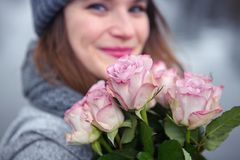 Young woman outdoors with bouquet of pink roses. Portrait of beautiful young woman outdoors with bouquet of pink roses Royalty Free Stock Photography