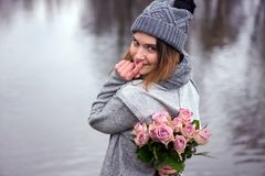 Young woman outdoors with bouquet of pink roses. Portrait of beautiful young woman outdoors with bouquet of pink roses Royalty Free Stock Photo