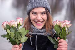 Young woman outdoors with bouquet of pink roses. Portrait of beautiful young woman outdoors with bouquet of pink roses Stock Photos