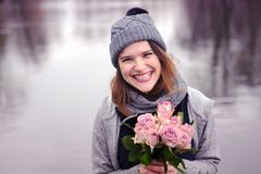Young woman outdoors with bouquet of pink roses. Portrait of beautiful young woman outdoors with bouquet of pink roses Royalty Free Stock Image