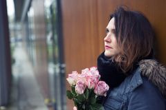Young woman outdoors with bouquet of pink roses. Portrait of beautiful young woman outdoors with bouquet of pink roses Royalty Free Stock Photos