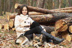 Young woman outdoors with dog. By log pack Stock Images