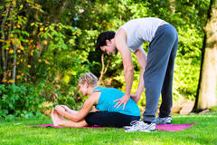 Young woman outdoors doing yoga with trainer Royalty Free Stock Photos