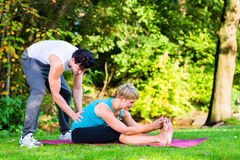 Young woman outdoors doing yoga with trainer Stock Photos