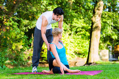 Young woman outdoors doing yoga with trainer Royalty Free Stock Image