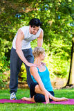 Young woman outdoors doing yoga with trainer Royalty Free Stock Images