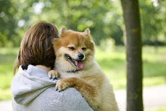 A young woman outdoors, holding her dog Royalty Free Stock Photo