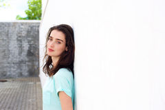 Young woman outdoors leaning against white wall Royalty Free Stock Photos