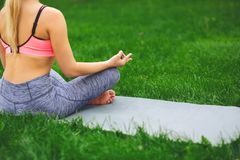 Young woman outdoors, relax meditation pose. Young woman outdoors, meditation exercises, back view, crop. Girl does bufferfly pose for relaxation. Wellness Stock Image