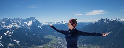 Young woman with outstretched arms, enjoying mountain excursion. Young woman enjoying mountain excursion in the bavarian alps at early springtime. view to Royalty Free Stock Photo