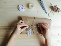 Young woman, owner of  sewing small business wrapping an parcel for delivery. Gift wraping idea. Royalty Free Stock Photos