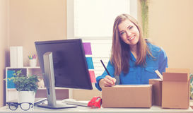 Young woman packing boxes to be shipped. In her home office stock images