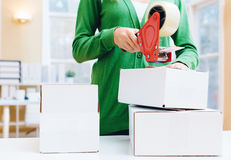 Young woman packing boxes to be shipped. In her home office royalty free stock photo