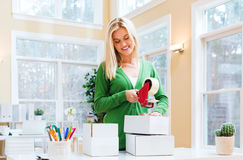 Young woman packing boxes to be shipped. In her home office stock photography