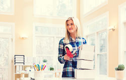 Young woman packing boxes to be shipped. In her home office stock image