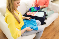 Young woman packing clothes into travel bag Stock Photos