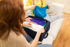 Young woman packing clothes into travel bag Royalty Free Stock Images