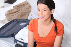 Young woman packing her luggage Stock Images