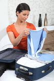 Young woman packing her suitcase Royalty Free Stock Images