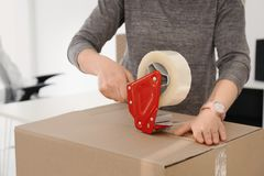 Young woman packing moving box indoors. Closeup stock images