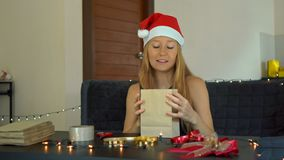 A young woman packing presents. Present wrapped in craft paper with a red and gold ribbon for christmas or new year. Woman makes an advent calendar for her stock video footage