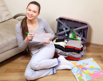 Young woman packing suitcase Stock Photos