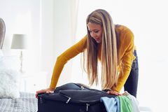 Young woman packing suitcase Stock Images