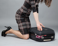 Young woman packing suitcase for travel Royalty Free Stock Images