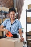 Woman taping box ready to be shipped. Young woman packing and taping carton boxes to be shipped in her office royalty free stock images