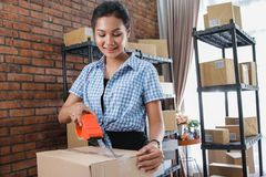 Woman taping box ready to be shipped. Young woman packing and taping carton boxes to be shipped in her office royalty free stock photo