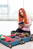The young woman packing for travel vacation Stock Image