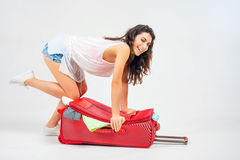 Young woman packs her things, clothes at full luggage Stock Images