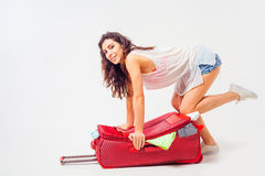 Young woman packs her things, clothes at full luggage Stock Photos