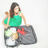 Young woman packs her things, clothes at full luggage Royalty Free Stock Image