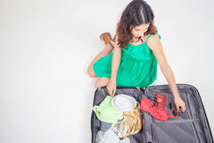 Young woman packs her things, clothes at luggage Stock Photo
