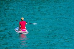 Young Woman on Paddle Board at the lake. SUP. View from back.  stock photo