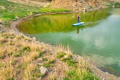 Young woman on paddle board SUP at lake Iacobdeal, Romania, paddling near the shoreline, on tranquil, pristine waters, at sunset.  royalty free stock photo