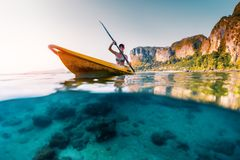 Young woman paddles kayak. In a tropical sea. Splitted shot with underwater stones view royalty free stock photos
