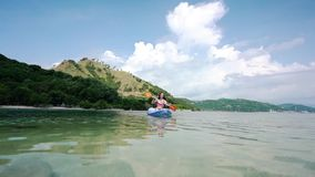 Young woman paddling a canoe on the sea during summer vacation in Indonesia. Woman paddling with a double-bladed paddle a canoe on the sea during summer vacation stock footage