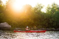 Young Woman Paddling the Red Kayak in Beautiful Lagoon with Green Trees and Stones at Warm Summer Sunset Royalty Free Stock Photography