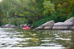 Young Woman Paddling Red Kayak in Beautiful Lagoon with Green Trees and Stones Stock Photos