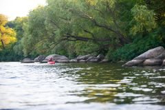 Young Woman Paddling Red Kayak in Beautiful Lagoon with Green Trees and Stones Stock Image