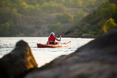 Young Woman Paddling the Red Kayak on Beautiful River or Lake in the Mountains. Young Woman Paddling the Red Kayak on the Beautiful River or Lake in the Royalty Free Stock Image