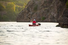 Young Woman Paddling the Red Kayak on Beautiful River or Lake near High Rocks. Young Woman Paddling the Red Kayak on the Beautiful River or Lake near High Rocks Royalty Free Stock Photography