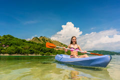 Young woman paddling during vacation in an idyllic travel destin. Happy young woman paddling a canoe on shallow water during vacation in an idyllic travel Royalty Free Stock Image