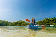 Young woman paddling during vacation in an idyllic travel destination. Happy young woman paddling a canoe on shallow water during vacation in an idyllic travel Stock Image