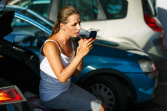 Young woman paint her lips sitting on the trunk of a car on the Royalty Free Stock Photos
