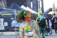 Young woman painted with colored powder. Young girl painted completely with differently colored powder laughing at the Color Run event on April 26 in Bucharest Stock Photo