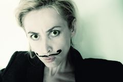 Young woman with painted mustache wearing jacket Stock Photos