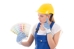 Young woman painter in blue builder uniform choosing color isola Stock Photo